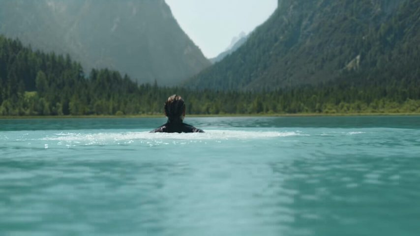 A woman in the water of a mountain lake